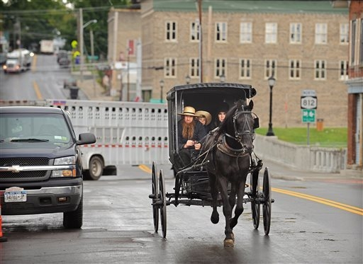FILE - An Amish family rides along Route 812 in Heuvelton, N.Y., near the command center at the Heuvelton Volunteer Fire Department, Friday, Aug. 15, 2014. The investigation continues into the abd ...