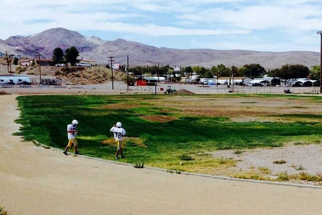 Two Beatty High football players walk across the mostly barren football field on their way to practice at the school's baseball diamond. Monsoon rains in July washed away new grass seed from the f ...