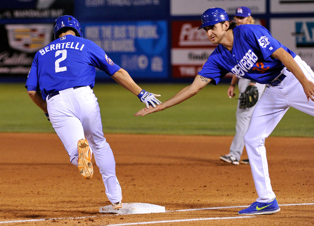 Las Vegas' Anthony Seratelli (2) receives a slap on the hand by John Lannan as he rounds first base after hitting a grand slam homerun during the 2nd inning of a baseball game  against the Round R ...