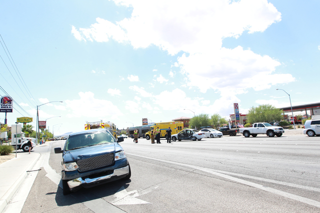 Clark County Fire Department and police respond to a crash involving a truck, left, and a sedan, center, at Boulder Highway and Russell Road in Las Vegas on Wednesday, Aug. 20, 2014. Police closed ...