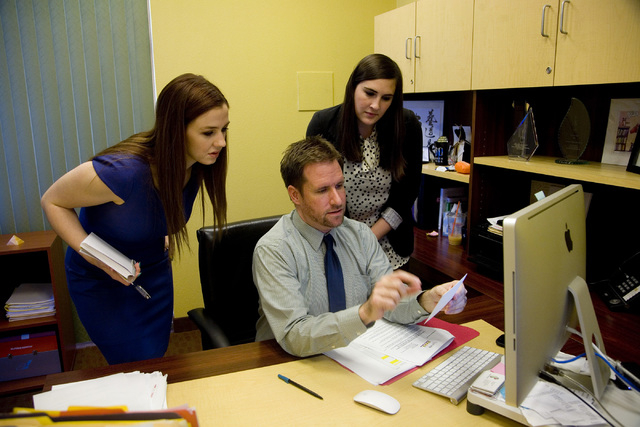 Jasen Woehrle, senior vice president of The Firm Public Relations, center, edits ad content with Public Relations Coordinator Annie Waggoner, left, and Assistant Public Relations Specialist Eleni  ...