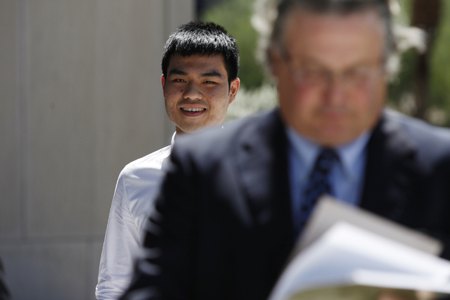 Darren Phua, left, walks to Lloyd George Federal Courthouse in Las Vegas with his attorney David Chesnoff for his arraignment Tuesday, Aug. 5, 2014. Phua's father Paul is the alleged ringleader of ...
