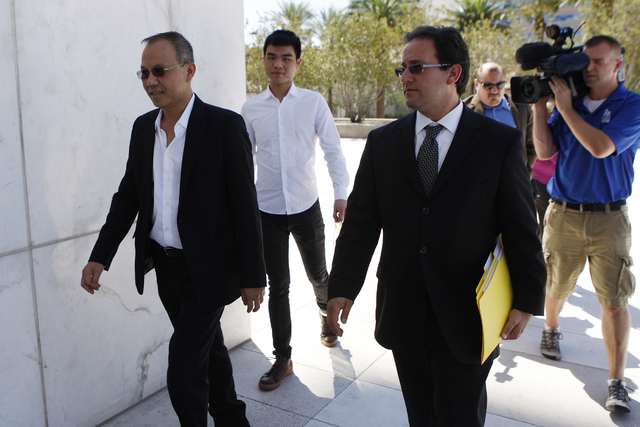 Paul Phua, left, and his son Darren, center, walk to Lloyd George Federal Courthouse in Las Vegas with their attorneys Richard Schonfeld, right, and David Chesnoff, not in the picture, for their a ...