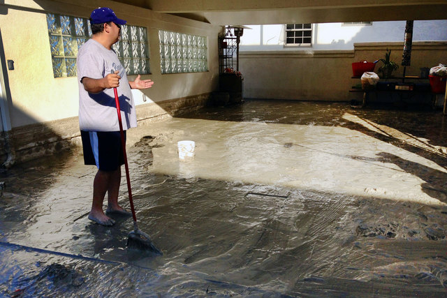 Hector Brown sweeps out his aunt and uncle's house in Seal Beach, California, on Wednesday, Aug. 27, 2014. The house and garage was flooded by a foot of water and muddy sand late Tuesday night aft ...