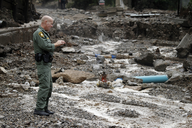Las Vegas Metropolitan police officer William Corder stands on what was Rainbow Canyon Road in the Rainbow Subdivision on Mount Charleston on Monday, July 28, 2014. The road was washed away by fla ...