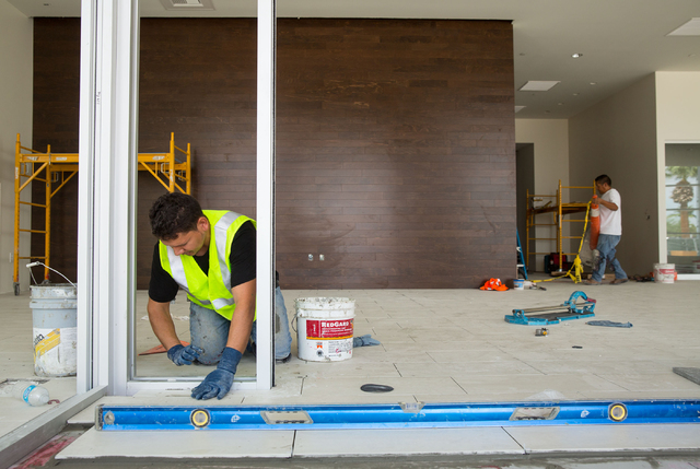 Luis Rojas, left, puts tile in the new entrance of Park Place Infiniti, located at 5605 W. Sahara Ave., Wednesday, Aug. 13, 2014. The dealership is adding a 20,000-square-foot building and renovat ...