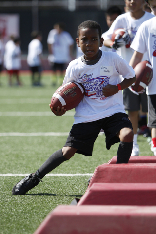 "Juan Kinley, 10, runs the ball during a drill at the Royal Purple Las Vegas Bowl Youth Football Clinic at Bill ""Wildcat"" Morris Rebel Park at UNLV Tuesday, Aug. 5, 2014. (Erik Verduzco/L ..."