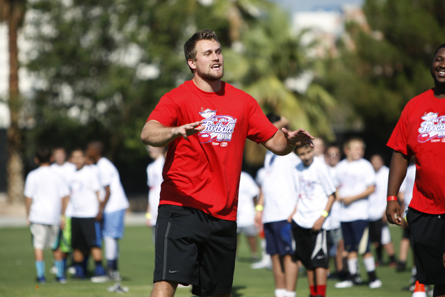 "UNLV's Taylor Barnhill (16) starts a Rebels chant during the starts of the Royal Purple Las Vegas Bowl Youth Football Clinic at Bill ""Wildcat"" Morris Rebel Park at UNLV Tuesday, Aug. 5,  ..."