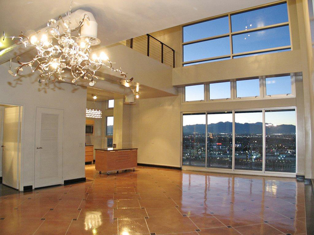 Courtesy photo  The open great room area of the two-level resale penthouse at Newport Lofts features custom flooring, exposed ductwork and floor-to-ceiling windows.