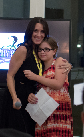 Hannah Newmaker, right, receives a hug from Deanna Iniguez, left, after finishing a speech at a White Horse Youth Ranch gala event July 19 in Las Vegas. The ranch is a nonprofit that inspires and  ...