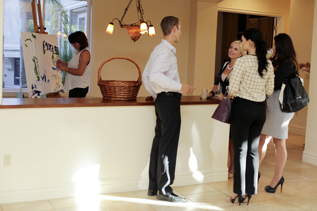 Luxury Realtor Rob Jensen talks to clients at a party he held in a Summerlin home he has listed for a client.