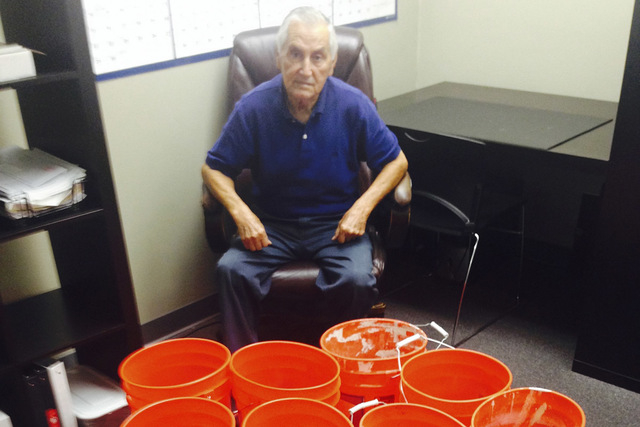 This image provided by Andres Carrasco shows him in his office in Los Angeles, July 31, 2014 with buckets of change he won as a partial settlement in a 2012 lawsuit against Adriana's Insurance S ...