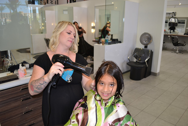 Sylist Desiree Dorsett blow drys the hair of Libby Waltermeyer during the Cure 4 The Kids Foundation's Haircut-a-Thon Aug. 24 at Mosaic Salon in Boca Park, 730 S. Rampart Blvd. Stylists and nail ...