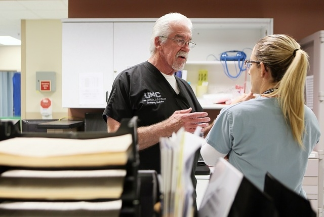 University Medical Center's Adult Emergency Room Chief of Staff Dr. Dale Carrison, center, speaks with fourth-year medical student Kylie Conroy, about the condition of their patient while w ...