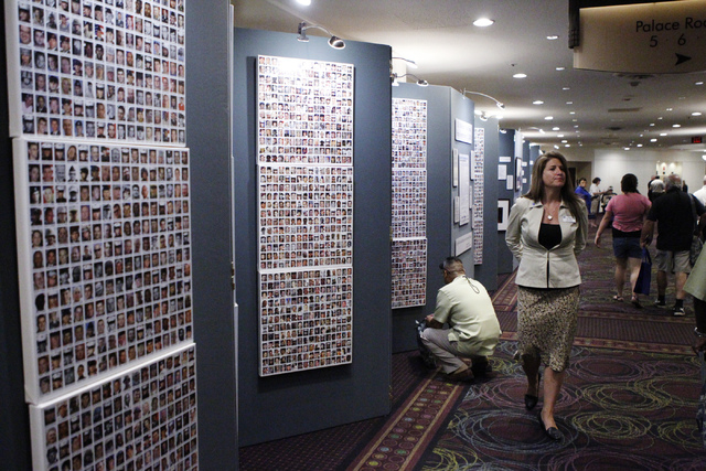 "Amy Roby, project manager of the ""Always Lost: A Meditation on War"" exhibit, walks along the exhibit on display during the National Disabled American Veterans and Auxiliary Convention at ..."