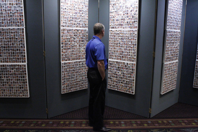 "National Service Officer Johnny DeLaughter looks at the ""Wall of the Dead"" panel as part of the ""Always Lost: A Meditation on War"" exhibit during the National Disabled American ..."