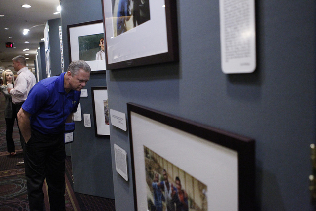 "National Service Officer Johnny DeLaughter looks at the Pulitzer Prize winning combat photographs on display with the ""Always Lost: A Meditation on War"" exhibit during the National Disab ..."