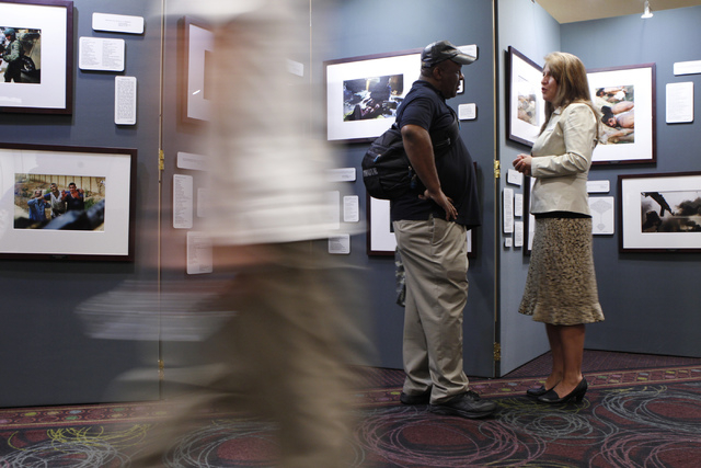 "Amy Roby, right, project manager of the ""Always Lost: A Meditation on War"" exhibit, speaks with U.S. Navy veteran Dwayne Ramey about the exhibit on display during the National Disabled A ..."