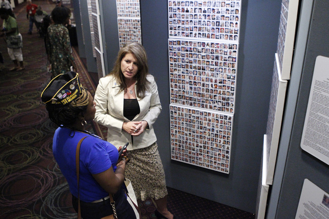 "Amy Roby, right, project manager of the ""Always Lost: A Meditation on War"" exhibit, speaks with Stacey Bryant about the exhibit on display during the National Disabled American Veterans  ..."