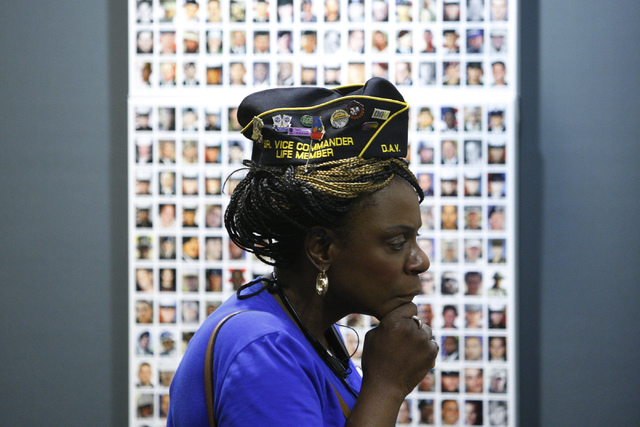"Stacey Bryant looks for a friend on the ""Wall of the Dead"" panel as part of the ""Always Lost: A Meditation on War"" exhibit during the National Disabled American Veterans and Au ..."
