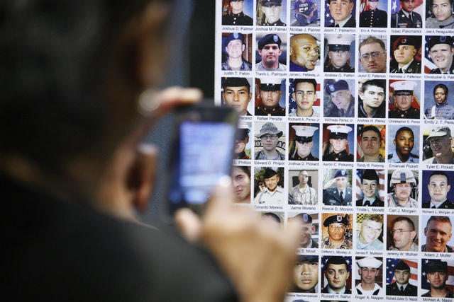 "Merline Leday-Mauney takes a photo of a photo of a family member on the ""Wall of the Dead"" panel as part of the ""Always Lost: A Meditation on War"" exhibit during the National D ..."