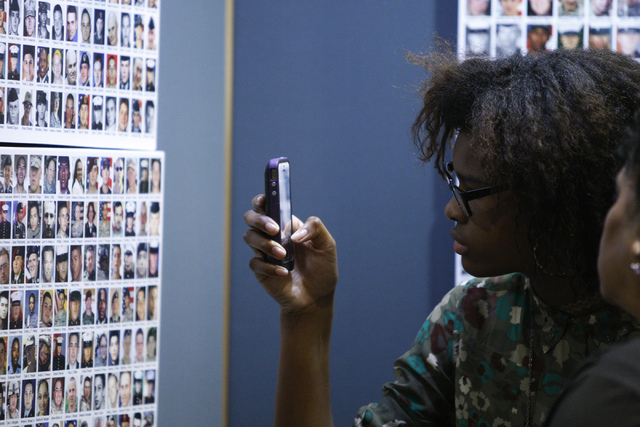 "Teresa Mauney takes a photo of a photo of her uncle Timothy Osbey on the ""Wall of the Dead"" panel as part of the ""Always Lost: A Meditation on War"" exhibit during the National  ..."