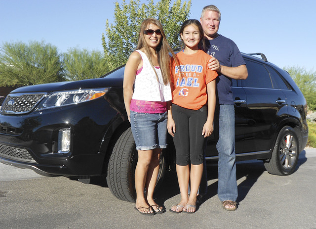 Courtesy photo From left, Sheilah, Angelique and Mike Vollmer pose by a 2015 Kia Sorento sport utility vehicle purchased from Findlay Kia at 5325 W. Sahara Ave.