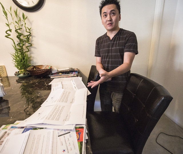Bobby Tran displays a kitchen table full of bills at his home in Las Vegas  on Monday, Aug. 25, 2014. Tran and his wife Ha Le lost their Health Plan of Nevada coverage because the exchange is tell ...