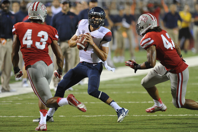 UNLV defenders Tim Hasson (43) and Peni Vea (42) tried to corral Arizona quarterback B.J. Denker (7) during last year's game at Sam Boyd Stadium, which the Rebels lost 58-13. Bishop Gorman grad An ...