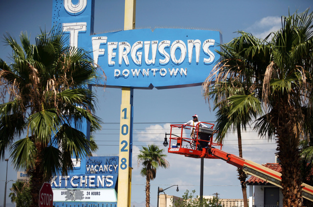 A worker operates a lift outside Fergusons Motel, located at 1028 East Fremont St. Friday, Aug. 1, 2014, in Las Vegas. Downtown Project plans to transform the closed hotel into a retail center. (R ...