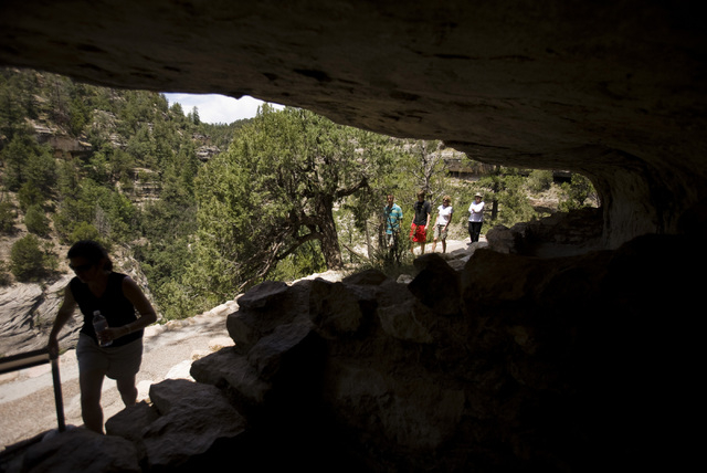 Hikers pass by a cliff dwelling at Walnut Canyon National Monument near Flagstaff, Arizona, on July 11, 2009. The dwellings were used by Sinagua Indians during the 12th and 13th centuries.  (JEFF  ...