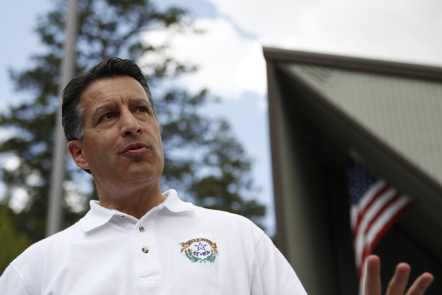 Gov. Brian Sandoval gives a press conference in front of the Mount Charleston Branch Library after his tour to the flood damaged area at the Rainbow Canyon subdivision at Mount Charleston Friday,  ...