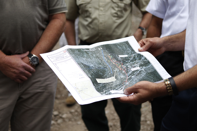Gov. Brian Sandoval holds a Rainbow subdivision project plan during a tour of the flood damaged area at Mount Charleston Friday, Aug. 1, 2014. (Erik Verduzco/Las Vegas Review-Journal)