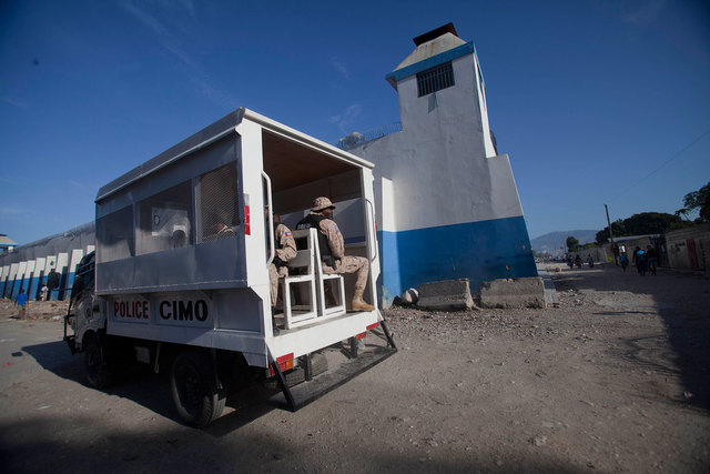 A police truck passes next to the main prison in Croix-des-Bouquets, Haiti, Monday, August 11, 2014. An attack on the prison on the outskirts of the capital to free the son of a prominent business ...