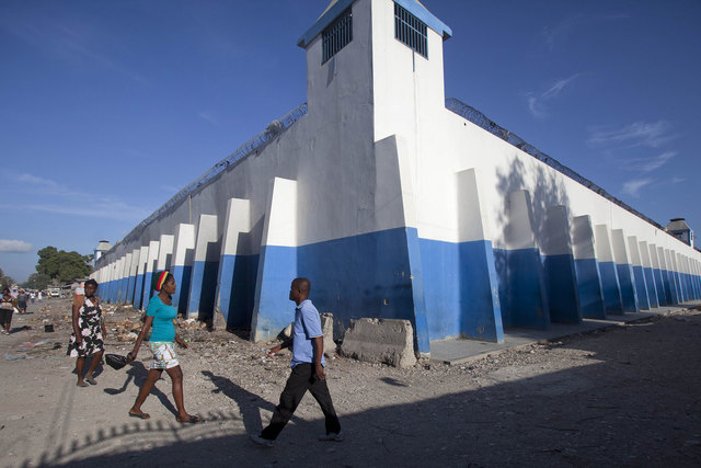 Pedestrians walk past a watch tower of the main prison in Croix-des-Bouquets, Haiti, Monday, August 11, 2014. An attack on the prison on the outskirts of the capital to free the son of a prominent ...