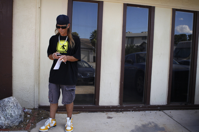 John Hastrich looks at his phone as he gets ready to do a media interview on the death of his girlfriend Terri Ham outside of his home, 3899 Almondwood Drive in Las Vegas Friday, Aug. 22, 2014. Ha ...