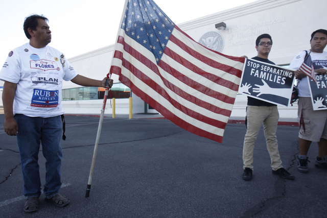 Activists Martin Macias, from left, with Edwin Gutierrez, and his son Jose, participate during a vigil to call on President Obama to use executive order powers to allow families to stay in the cou ...