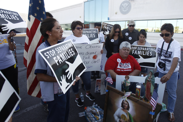 Immigration advocates say a prayer during a vigil to call on President Obama to use executive order powers to allow families to stay in the country legally at the U.S. Department of Homeland Secur ...