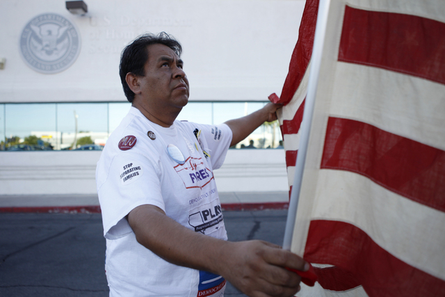 Activist Martin Macias displays an American flag during a vigil to call on President Obama to use executive order powers to allow families to stay in the country legally at the U.S. Department of  ...
