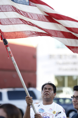 Activist Martin Macias waves an American flag during a vigil to call on President Obama to use executive order powers to allow families to stay in the country legally at the U.S. Department of Hom ...