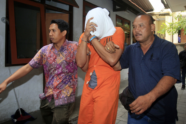 Indonesian police officers escort Tommy Schaefer, center, covering his face,  to a hospital for medical check Friday, Aug. 15, 2014.  The body of the 62-year-old American woman Sheila von Wiese-Ma ...