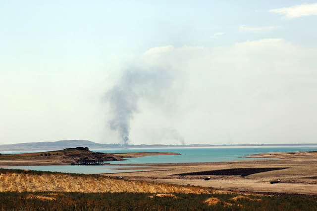 Smoke rises during airstrikes targeting Islamic State militants at the Mosul Dam outside Mosul, Iraq, Monday, Aug. 18, 2014. Boosted by two days of U.S. airstrikes, Iraqi and Kurdish forces on Mon ...