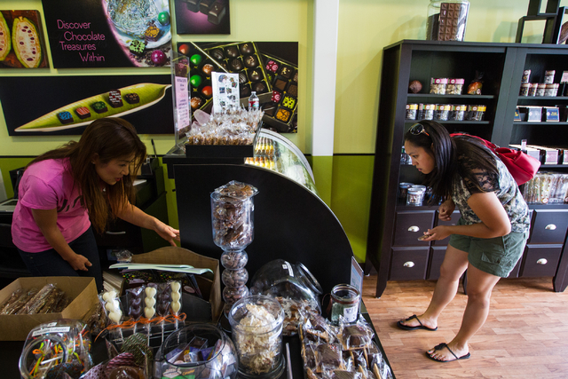 Chocolatier and business Owner Jin Caldwell, left, assists Toni Crowel of Moose Lake, Minn., at Jinju Chocolates in the Downtown Container Park in Las Vegas on Tuesday, July 15, 2014. (Chase Steve ...