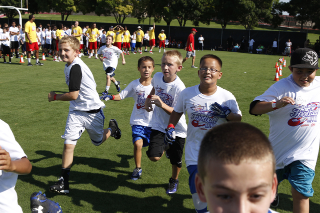 "Children run to their assigned practice areas during the  Royal Purple Las Vegas Bowl Youth Football Clinic at Bill ""Wildcat"" Morris Rebel Park at UNLV Tuesday, Aug. 5, 2014. (Erik Verduzco/Las Ve ..."