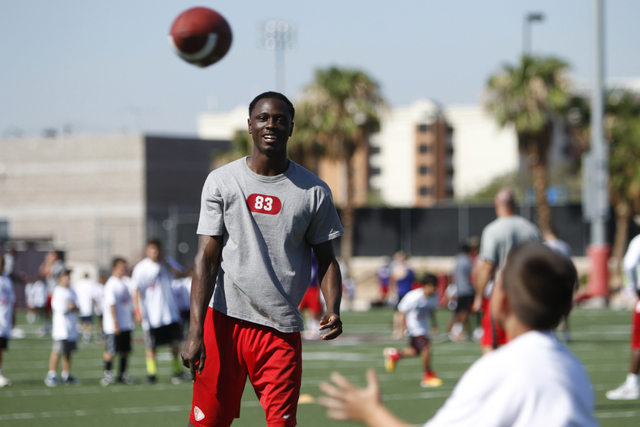 "UNLV's freshman Devonte Boyd (83) throws a pass during the Royal Purple Las Vegas Bowl Youth Football Clinic at Bill ""Wildcat"" Morris Rebel Park at UNLV Tuesday, Aug. 5, 2014. (Erik Verd ..."