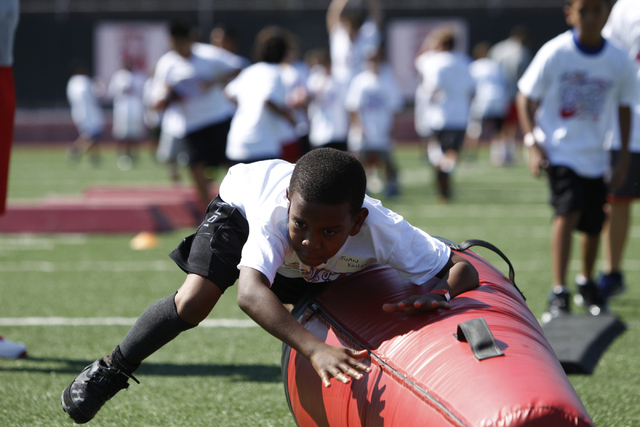 "Juan Kinley, 10, participates during a tackling drill at the Royal Purple Las Vegas Bowl Youth Football Clinic at Bill ""Wildcat"" Morris Rebel Park at UNLV Tuesday, Aug. 5, 2014. (Erik Ve ..."