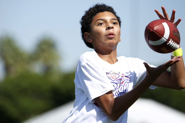 "Gevon Graham, 13, makes a catch during a pass drill at the Royal Purple Las Vegas Bowl Youth Football Clinic at Bill ""Wildcat"" Morris Rebel Park at UNLV Tuesday, Aug. 5, 2014. (Erik Verd ..."