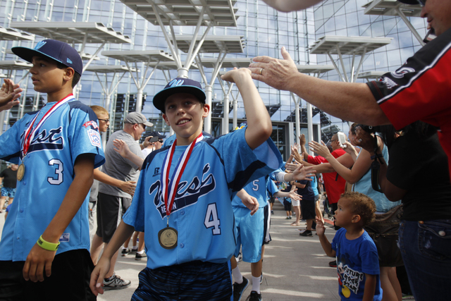 Mountain Ridge Little League players Dominic Clayton (3), left, and Drew Laspaluto (4), high five fans as the team leaves for their parade after being honored at Las Vegas City Hall in Las Vegas S ...