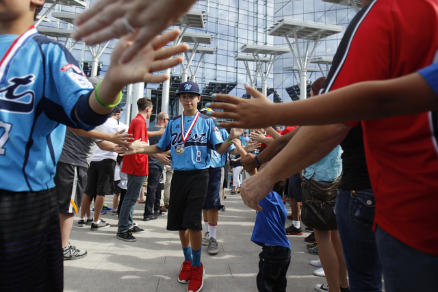 Mountain Ridge Little League player Dallan Cave (8), center, high fives fans as his team leaves for their parade after being honored at Las Vegas City Hall in Las Vegas Saturday, Aug. 30, 2014. (E ...