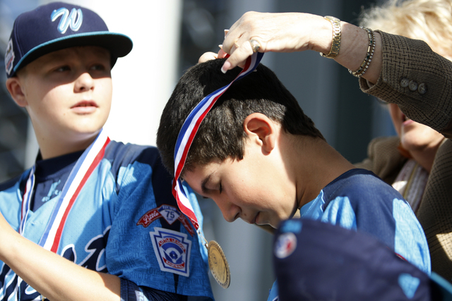 Mountain Ridge Little League player Josiah Cromwick (7), center, receives a medal from Las Vegas Mayor Carolyn Goodman during a ceremony to honor the team for their Little League World Series perf ...